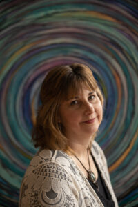 Portrait of artist Melynda Van Zee in front of a colorful spiral painting.
